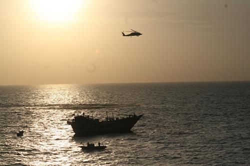 A U.S. Navy SH-60S Seahawk provides support to a visit, board, search and seizure team in a 7-meter rigid-hull inflatable boat, assigned to guided-missile destroyer USS Kidd. The VBSS team boarded an Iranian-flagged fishing dhow Al Molai after the dhow's master stated he was being held captive by pirates. The Kidd's VBSS team detained 15 suspected pirates who were reportedly holding a 13-member Iranian crew hostage for the last two months. The Kidd is conducting counter-piracy and maritime security operations while deployed to the U.S. 5th Fleet area of responsibility.